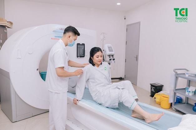 Kỹ thuật viên hướng dẫn người bệnh nằm lên bàn để chụp CT phổi