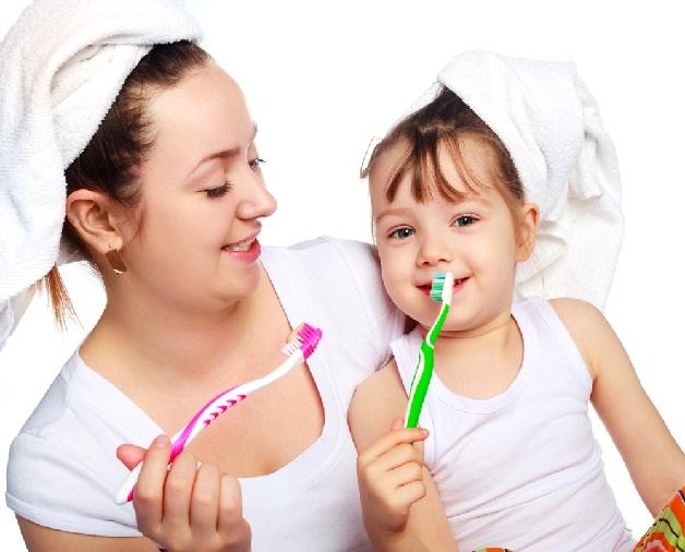 Bố mẹ làm sạch răng cho con rồi cho con súc miệng bằng nước muối ấm pha loãng