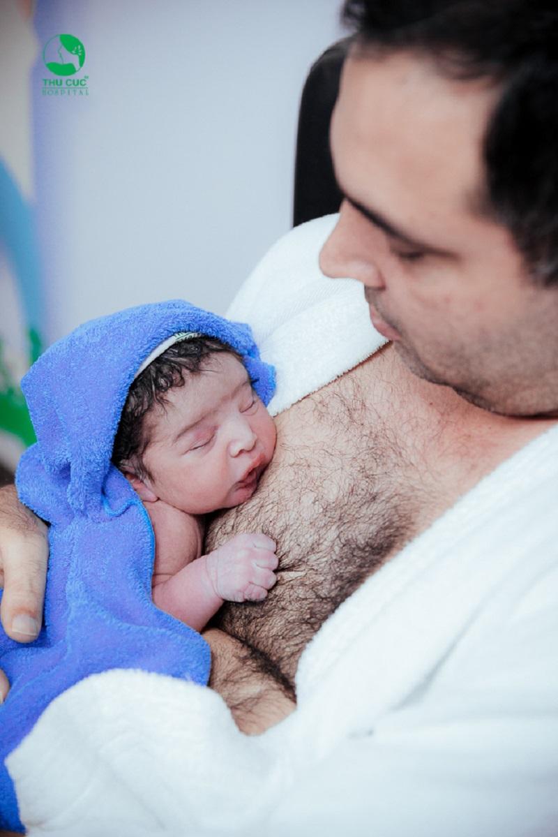 Em bé ngoan ngoãn nằm trên ngực bố khi được áp da.